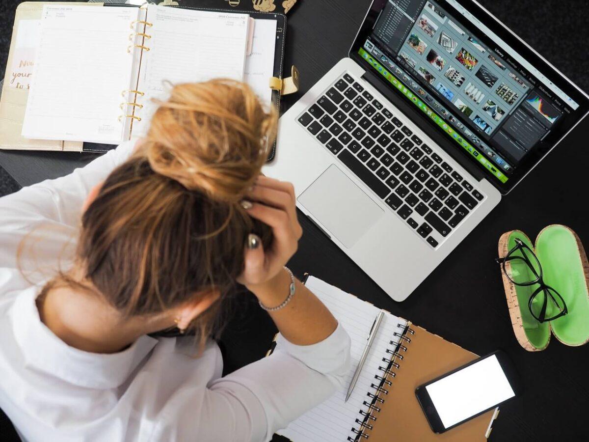 Dziewczyna-siedzi-zalamana-nad-ksiazkami-i-laptopem